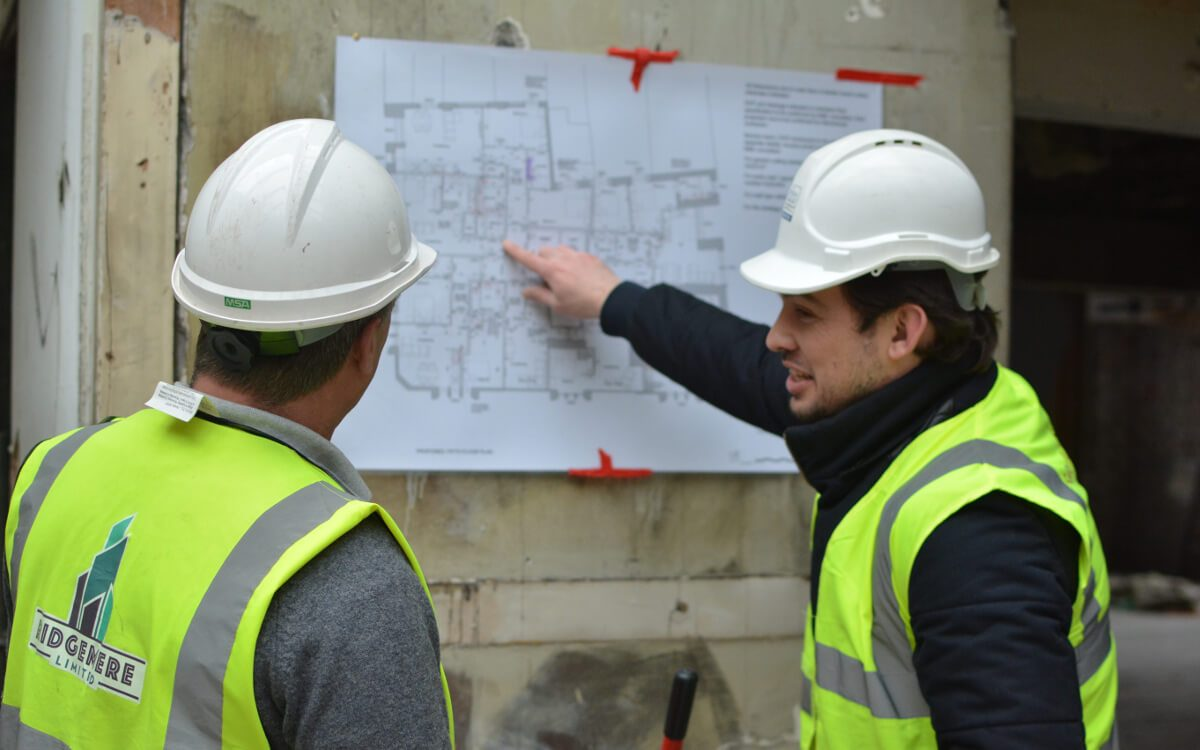 Jonathan Howell and customer wearing hi-vis vests and hard hats reviewing plans for Document E Design Advice