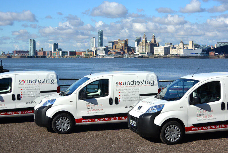 Three Soundtesting Vans parked on the Wirral with a background of Liverpool and blue sky