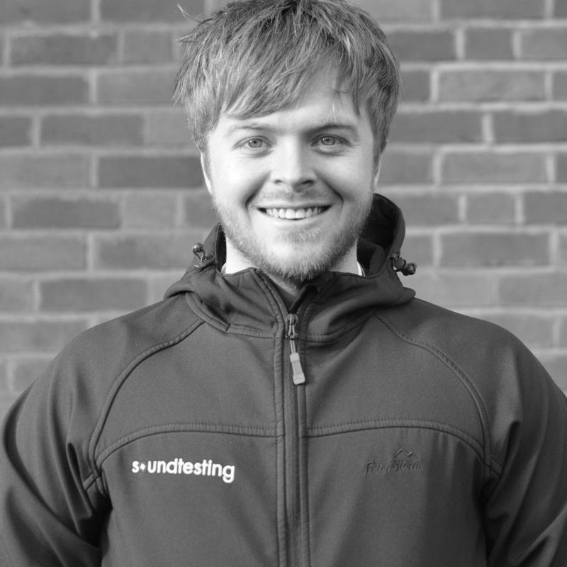Jack Holmes wearing a Soundtesting jacket, smiling at the camera